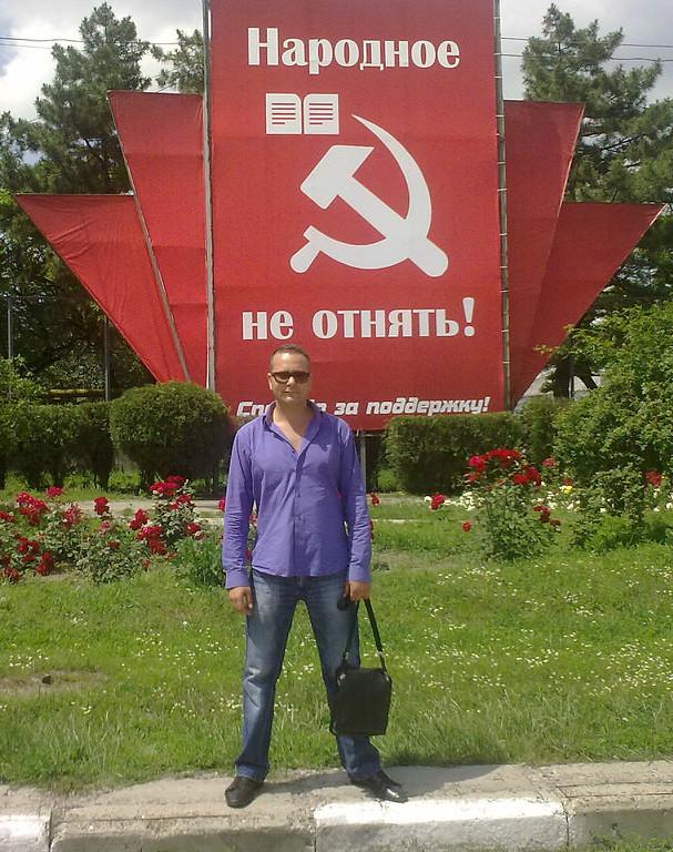 Serghei Izbaș pozează lângă panoul instalat de conducerea comunistă la Bălți // captură ok.ru